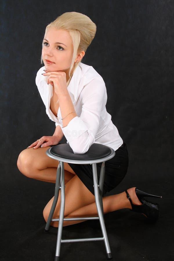 白肤金发椅子女孩倾斜 免版税库存照片