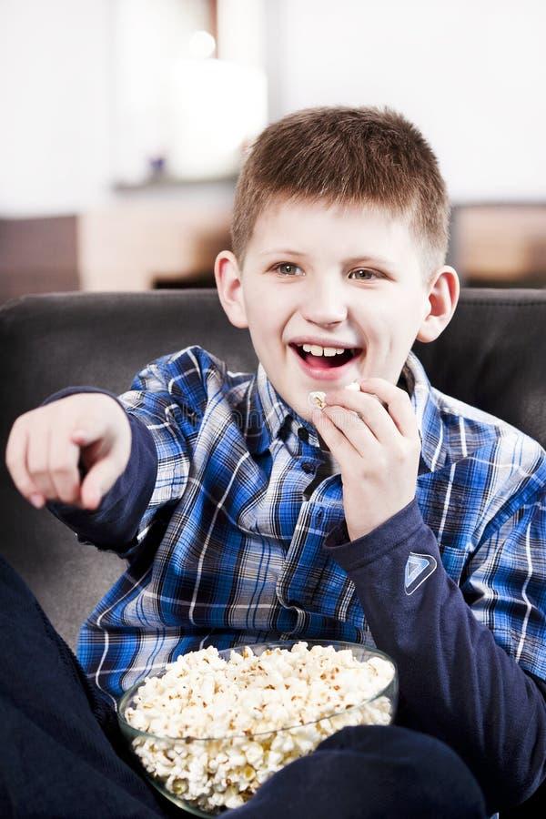白肤金发男孩吃愉快玉米花电视注意 库存图片