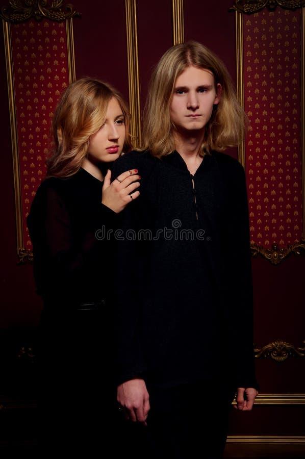 年轻白肤金发的人民夫妇在黑色穿戴了在一个暗室 图库摄影