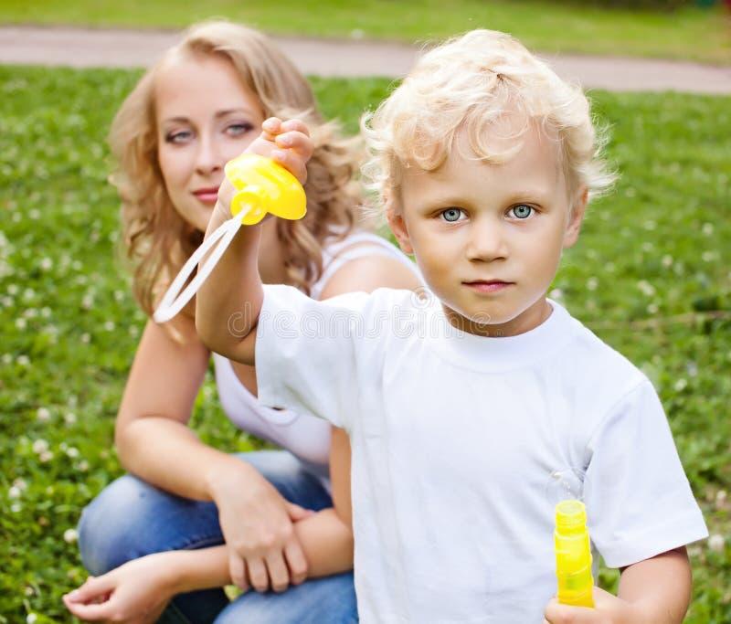 白肤金发的使用在公园的母亲和儿子 库存图片