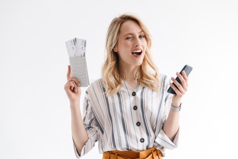 白肤金发的使用手机的年轻女人佩带的便服画象,当持旅行的票和护照时 免版税库存照片