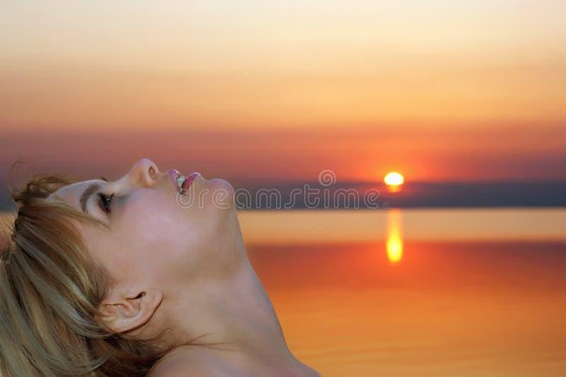 白肤金发的俏丽的日落年轻人 免版税库存图片
