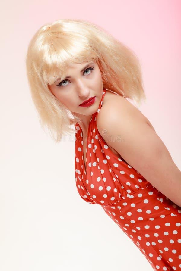 白肤金发的假发减速火箭的红色礼服的画象美丽的画报女孩。葡萄酒。 免版税库存图片