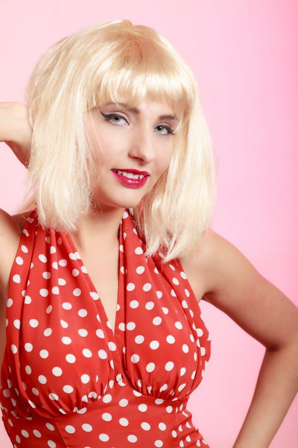 白肤金发的假发减速火箭的红色礼服的画象美丽的画报女孩 葡萄酒 免版税图库摄影