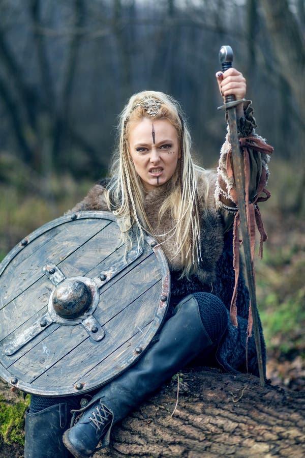白肤金发的北欧海盗战士妇女在有盾和剑的森林里 免版税库存图片