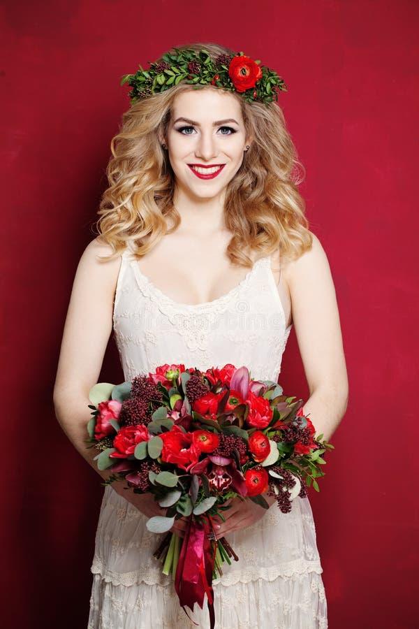 白肤金发的卷发妇女 有花的新娘 免版税库存图片