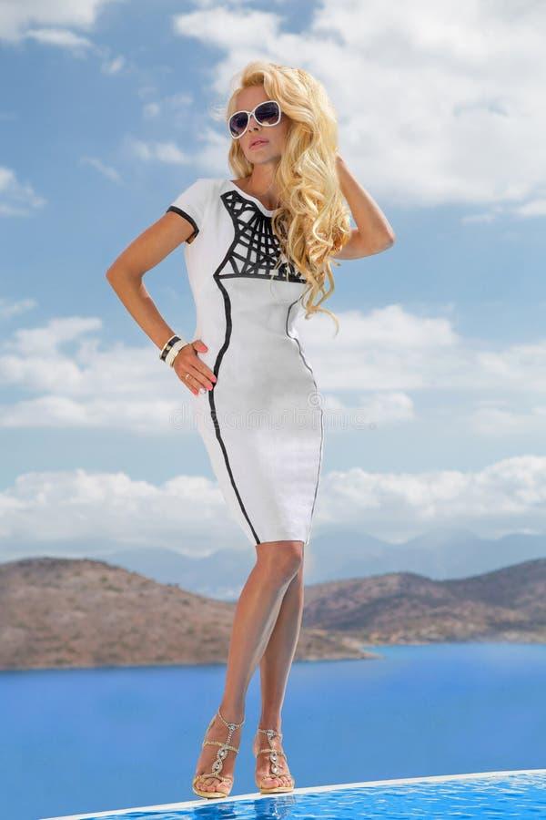 从白肤金发的卷曲长的头发的美丽的性感的少妇在短的白色富挑战性性感的高价衣服站立在盐 免版税图库摄影