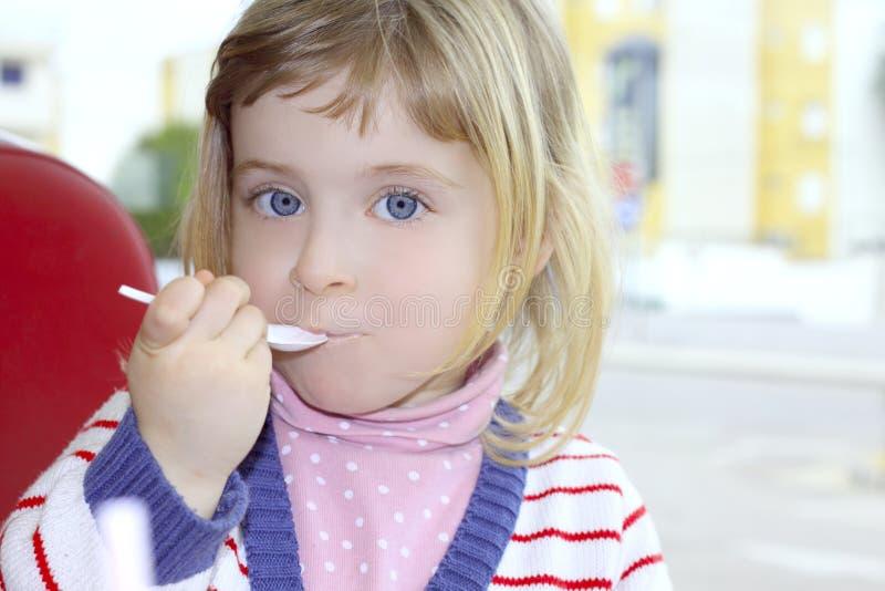 白肤金发的吃的女孩少许纵向匙子 库存照片