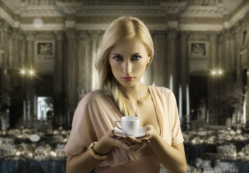 白肤金发的咖啡杯肉欲的妇女 免版税库存照片