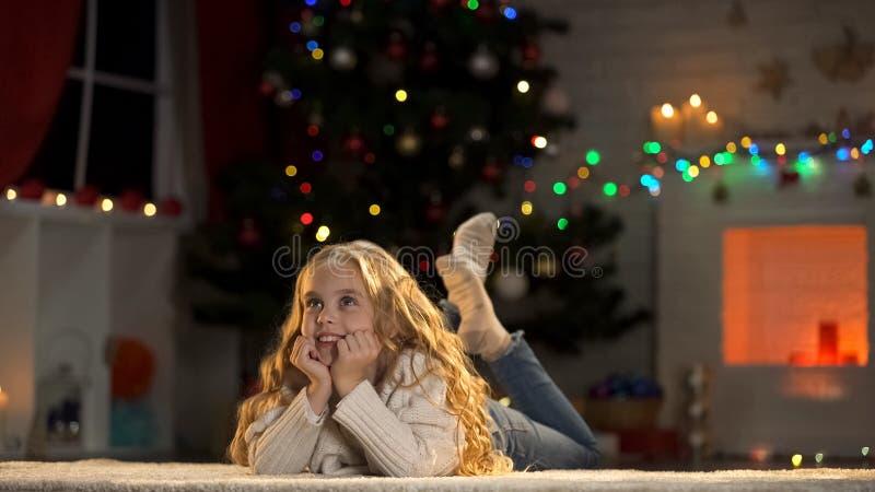 白肤金发的在圣诞树附近的女孩等待的礼物,考虑庆祝 免版税库存照片
