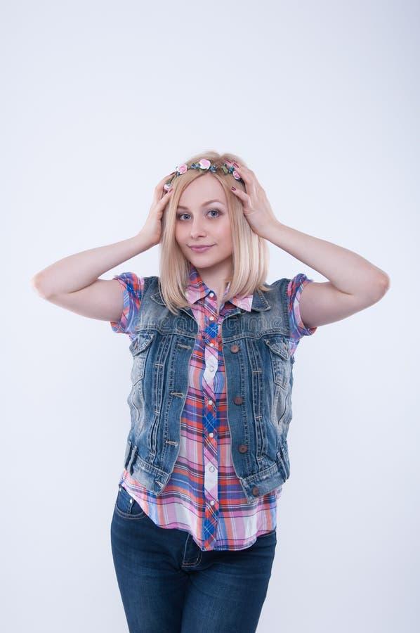 白肤金发的在她的头的女孩佩带的花花圈 背景概念花春天空白黄色年轻人 免版税图库摄影