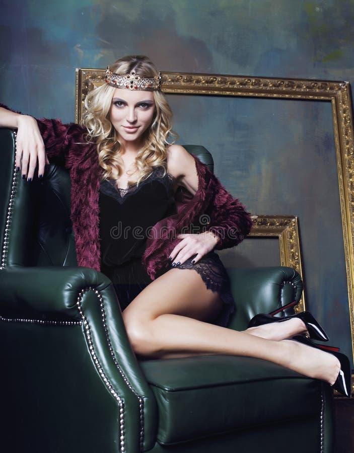 年轻白肤金发的在神仙的豪华内部的妇女佩带的冠与空的古董构筑总财富长的腿 免版税库存图片