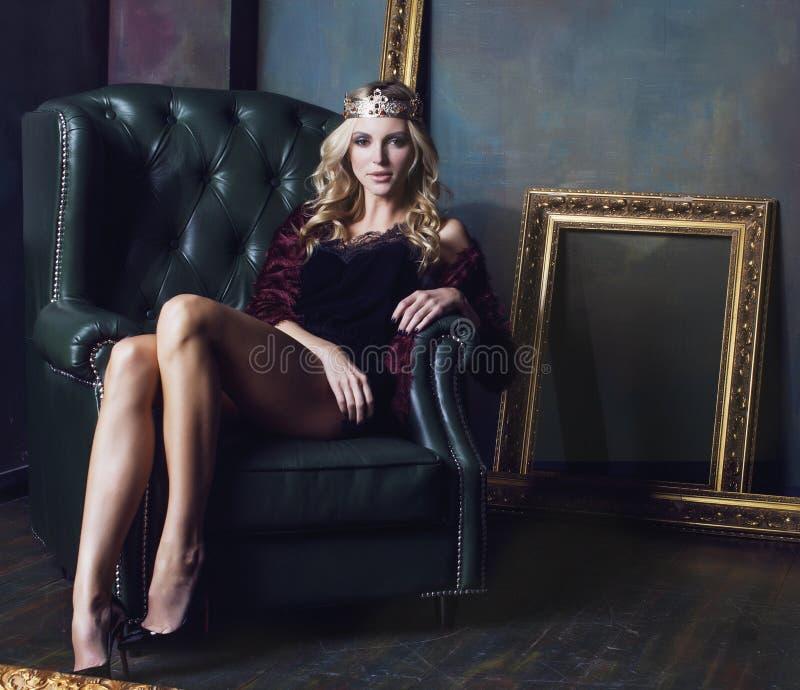 年轻白肤金发的在神仙的豪华内部的妇女佩带的冠与空的古董构筑总财富 图库摄影