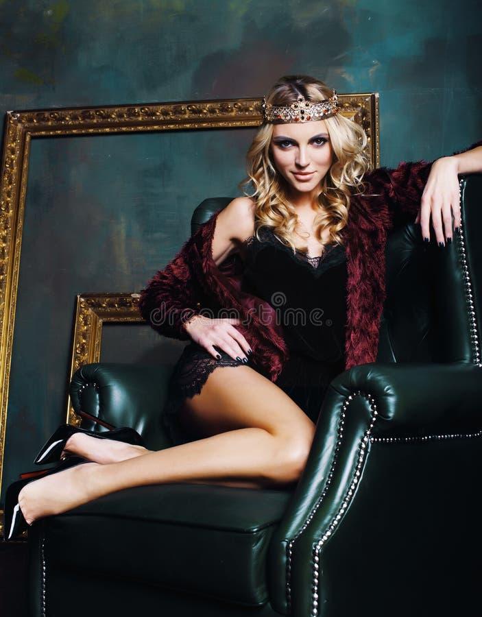 年轻白肤金发的在神仙的豪华内部的妇女佩带的冠与em 免版税库存图片