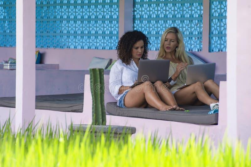 白肤金发的在网上工作与便携式计算机一起的妇女和拉丁混杂的女孩户外在米领域前面作为数字式游牧人星期五 免版税图库摄影