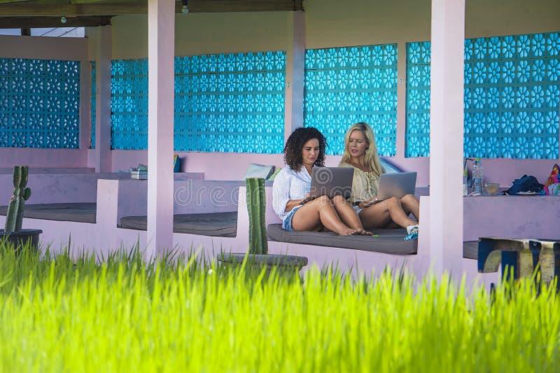 白肤金发的在网上工作与便携式计算机一起的妇女和拉丁混杂的女孩户外在米领域前面作为数字式游牧人星期五 库存图片