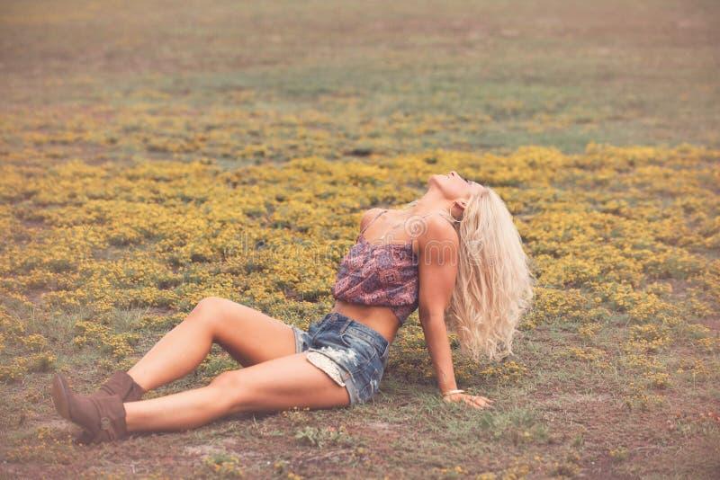 白肤金发的在领域的妇女简而言之和起动 库存图片