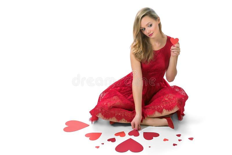白肤金发的坐华伦泰的妇女红色心脏被隔绝 免版税库存图片