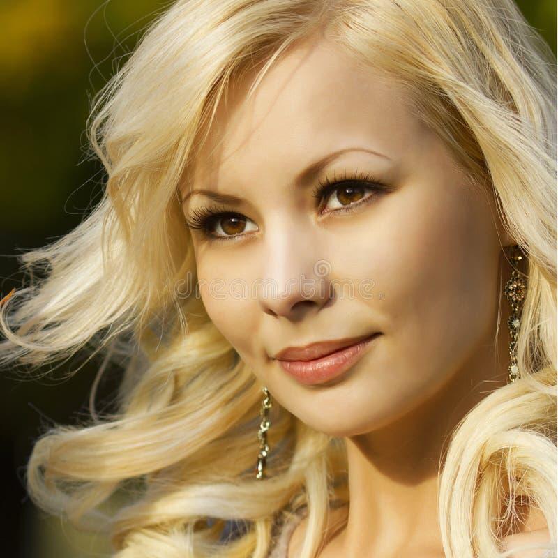 白肤金发的女孩。美丽的微笑的愉快的少妇画象外面。 免版税库存照片