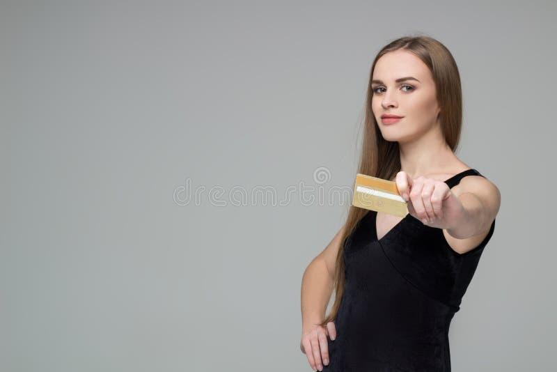 白肤金发的女孩举行金黄银行信用卡购物付款 免版税库存照片