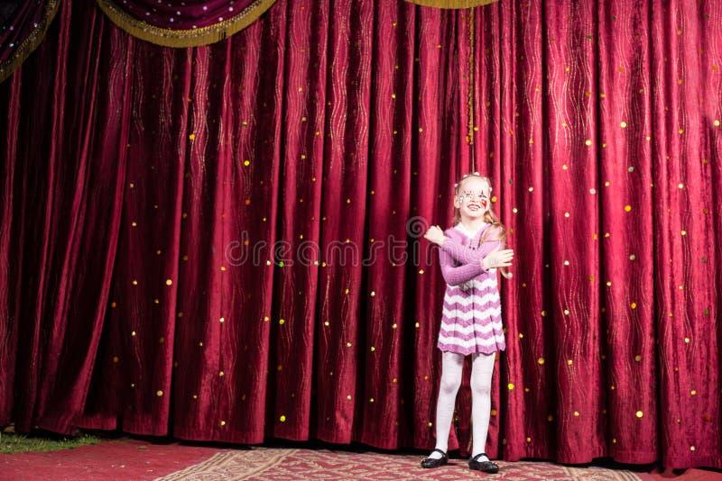 白肤金发的女孩佩带的小丑在阶段做站起来 库存图片