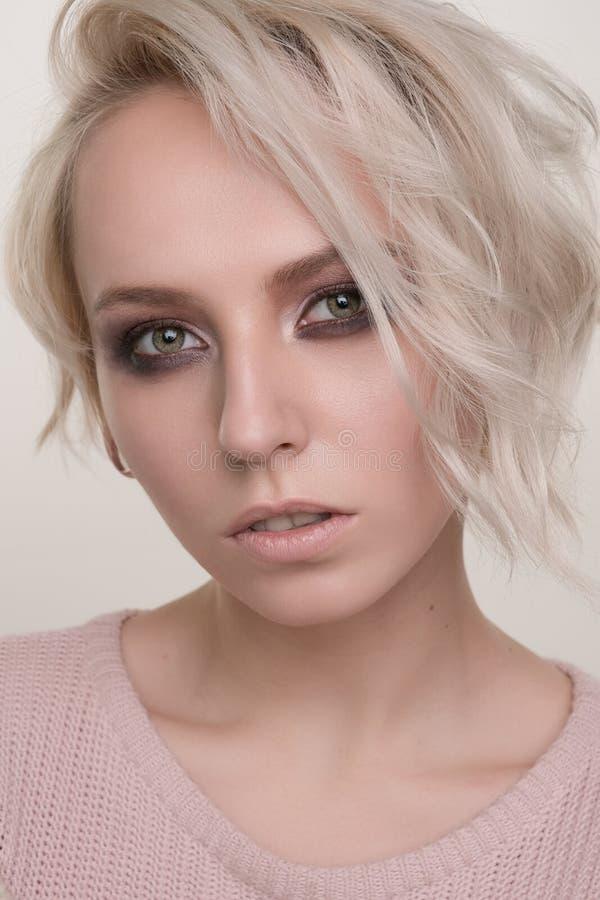 白肤金发的女孩和在看照相机,眼睛变窄的一件浅粉红色的毛线衣的短发特写镜头画象有黑眼睛构成的 免版税库存图片