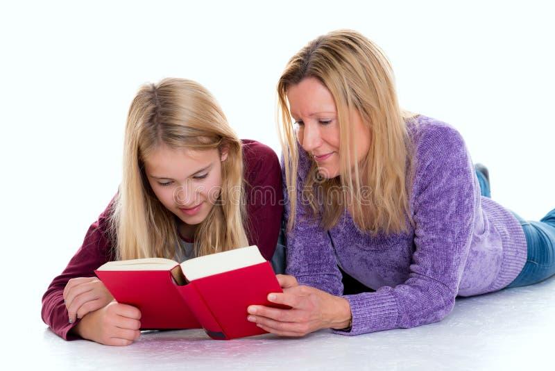 白肤金发的女孩和她的使用片剂个人计算机的母亲 库存照片