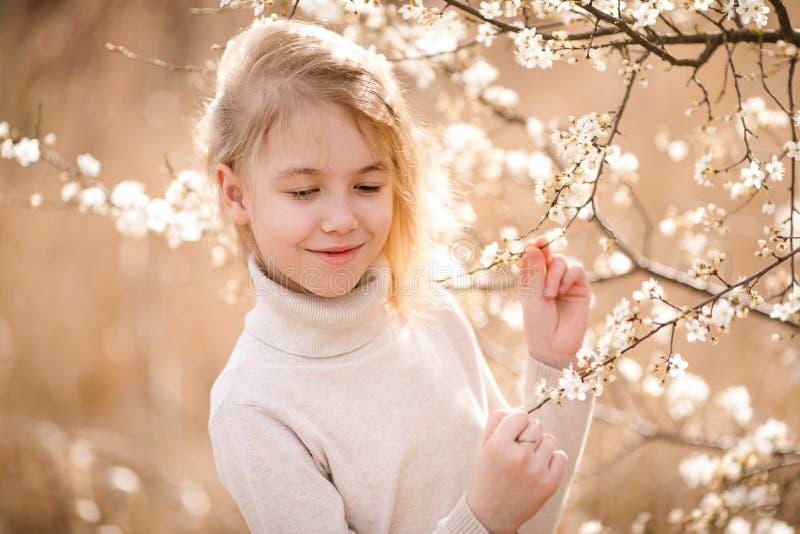 白肤金发的女孩在开花庭院里 与白花的春天背景 库存照片