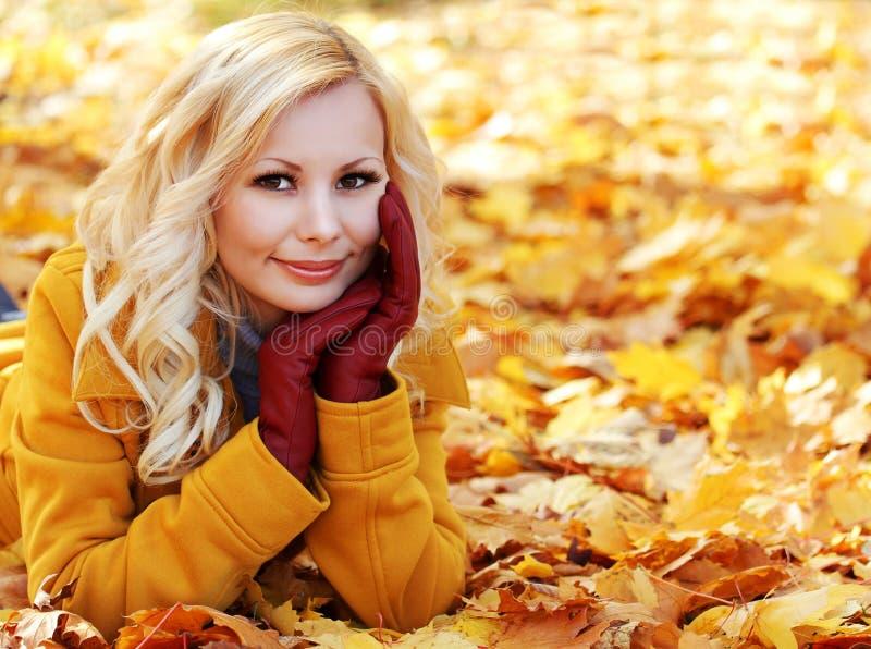 白肤金发的女孩在有槭树的秋天公园离开。美好的时尚 免版税库存照片