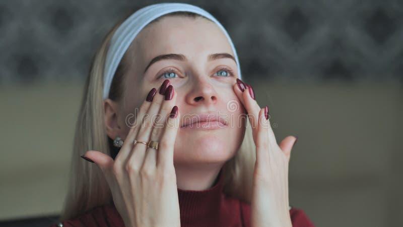 白肤金发的女孩在构成前应用在面孔的concealer 图库摄影