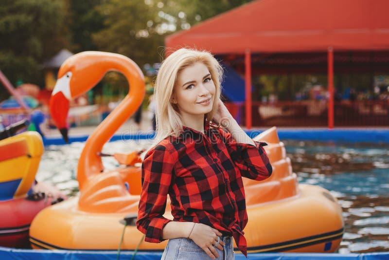 白肤金发的女孩在游乐园在夏天 免版税库存图片