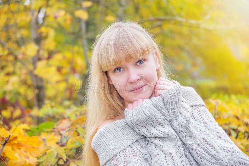 白肤金发的女孩在秋天公园 免版税库存图片