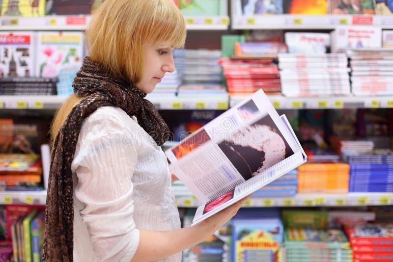 白肤金发的女孩在超级市场翻阅书 库存照片