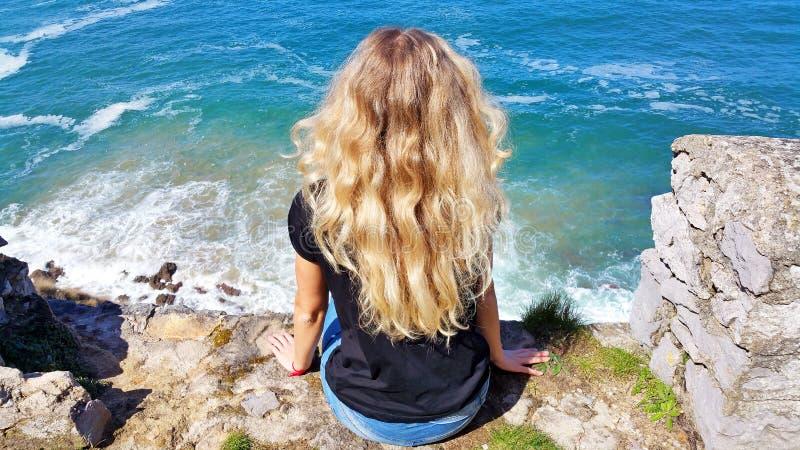 白肤金发的女孩坐岩石,看在水 图库摄影