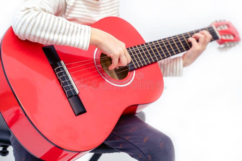 白肤金发的女孩坐并且弹红色吉他 免版税库存照片