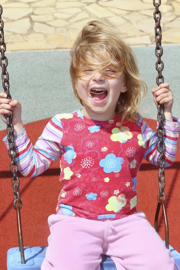 白肤金发的女孩头发一点杂乱公园摇&# 库存照片