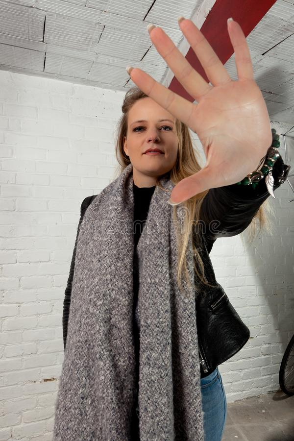 白肤金发的女孩手中止白色砖墙 图库摄影