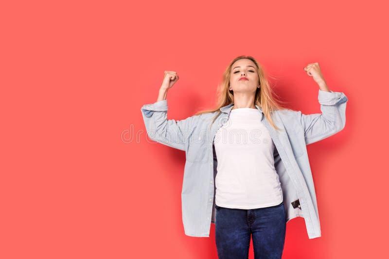 年轻白肤金发的女孩显示她在红色背景的力量 免版税库存照片