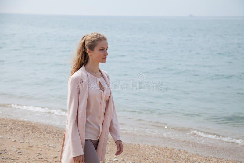 白肤金发的女孩沿沿海的海滩走 免版税库存照片