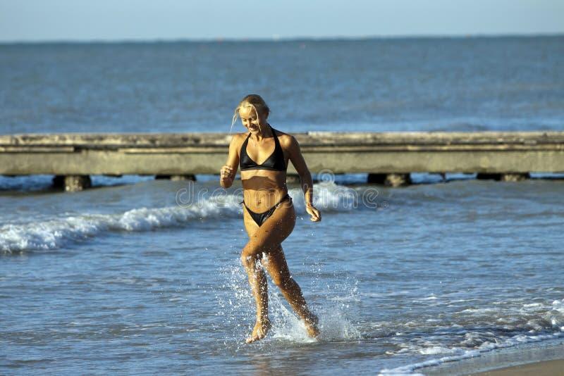 白肤金发的女孩海洋运行的性感 图库摄影