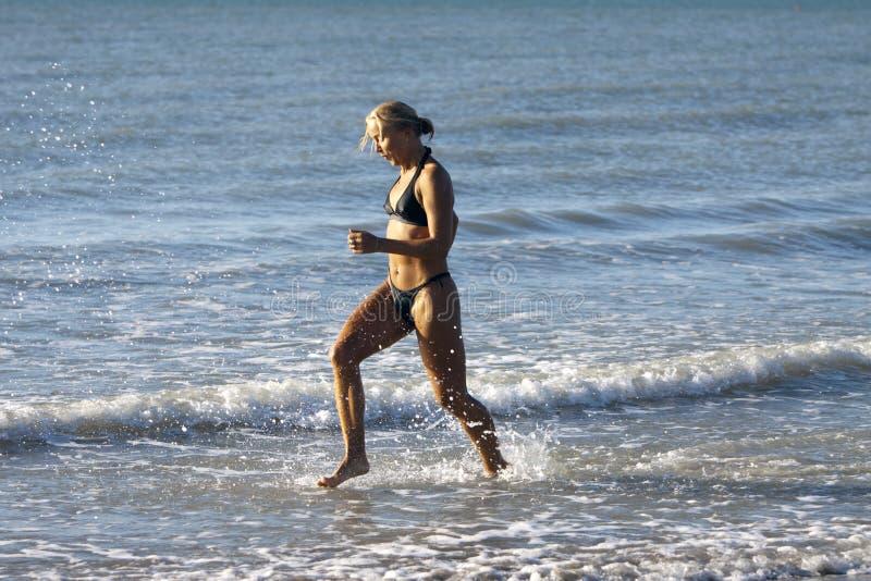 白肤金发的女孩海洋运行的性感 库存图片