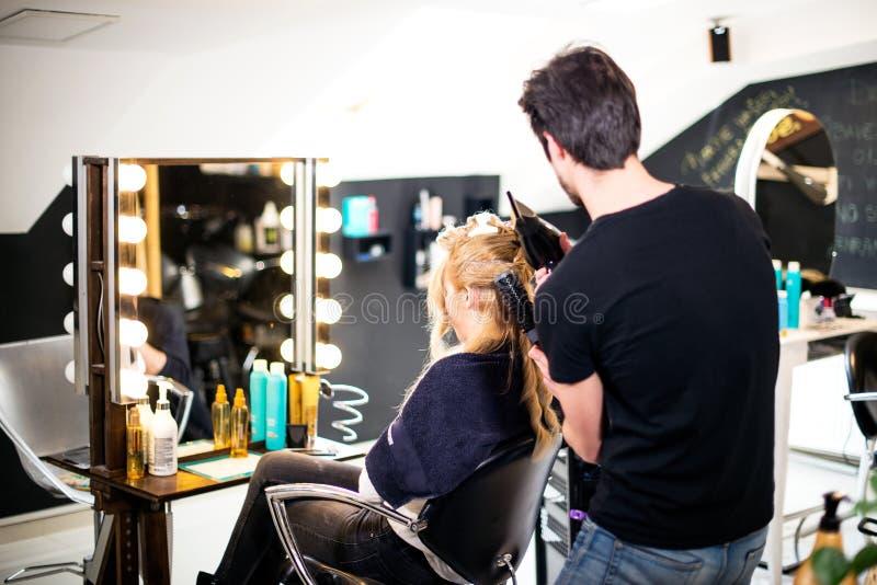 白肤金发的女孩的新的发型,由年轻美发师 免版税库存照片