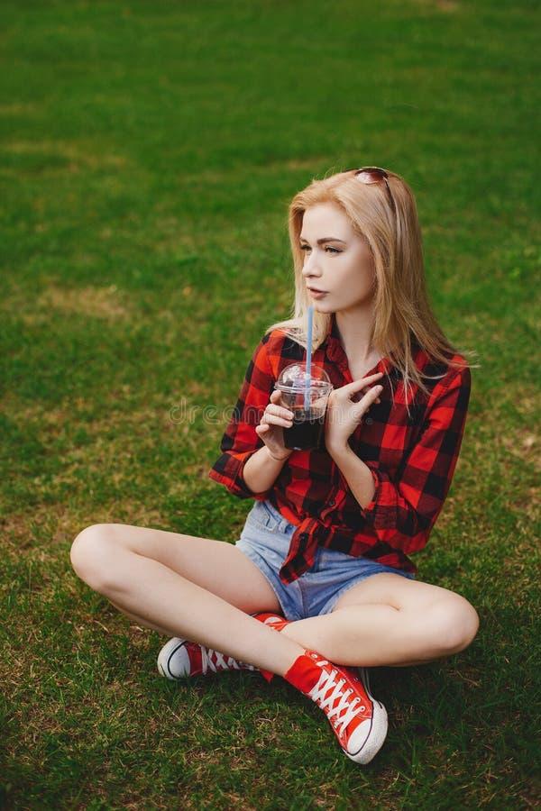 白肤金发的女孩简而言之在草的夏天 免版税图库摄影