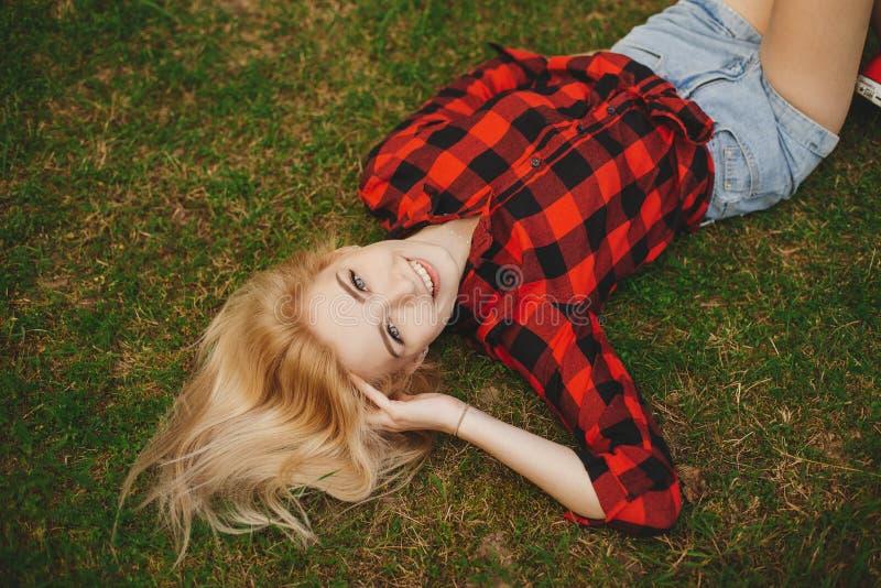 白肤金发的女孩简而言之在草的夏天 库存照片