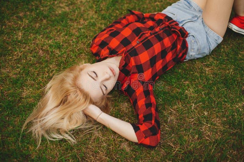 白肤金发的女孩简而言之在草的夏天 库存图片