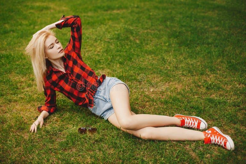 白肤金发的女孩简而言之在草的夏天 免版税库存图片