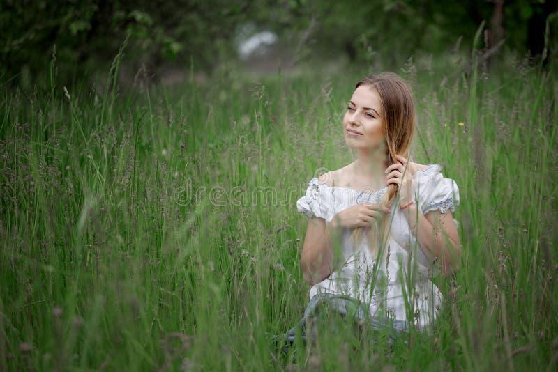 白肤金发的女孩简而言之坐草户外 免版税库存照片