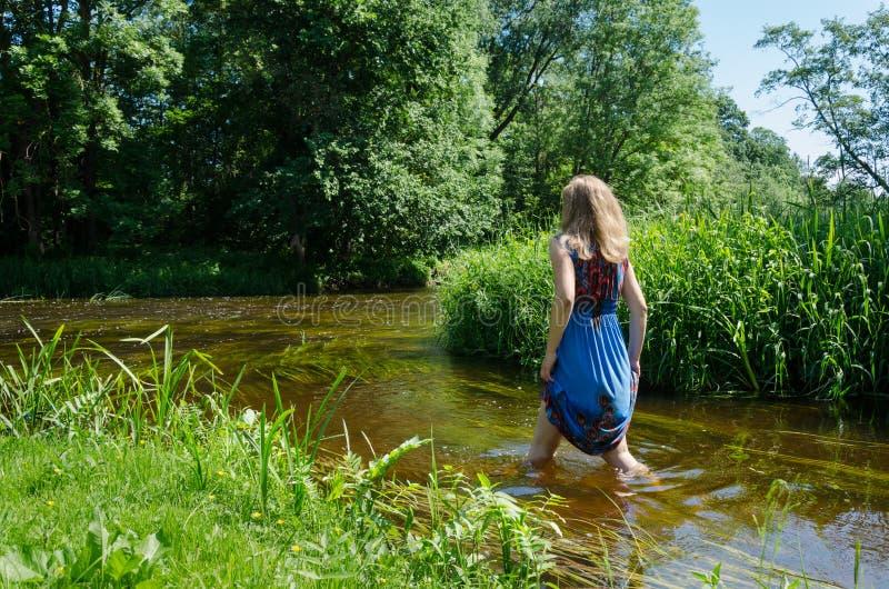 白肤金发的女孩蓝色呈杂色的礼服涉过流动的河 免版税图库摄影