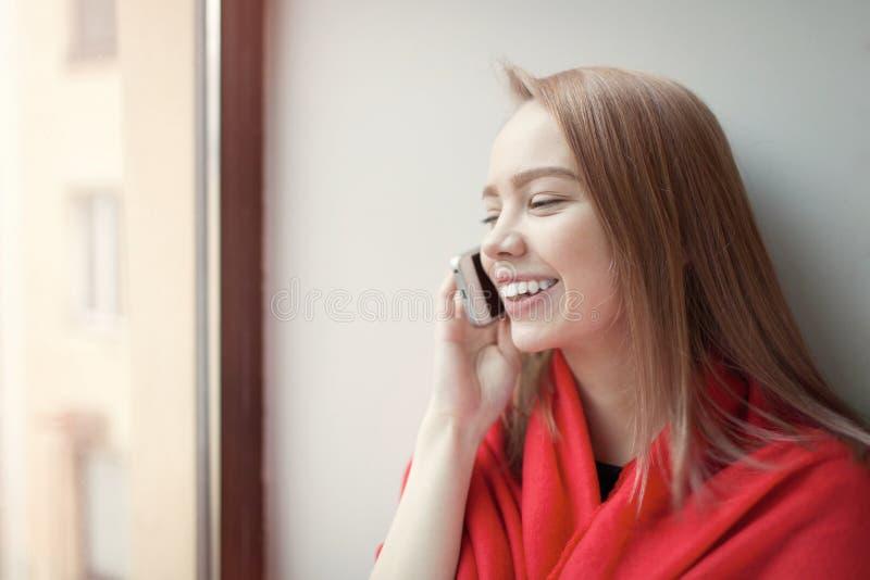 年轻白肤金发的女孩谈话在坐由窗口的电话,包裹在一条红色毯子 她是愉快和微笑 库存图片