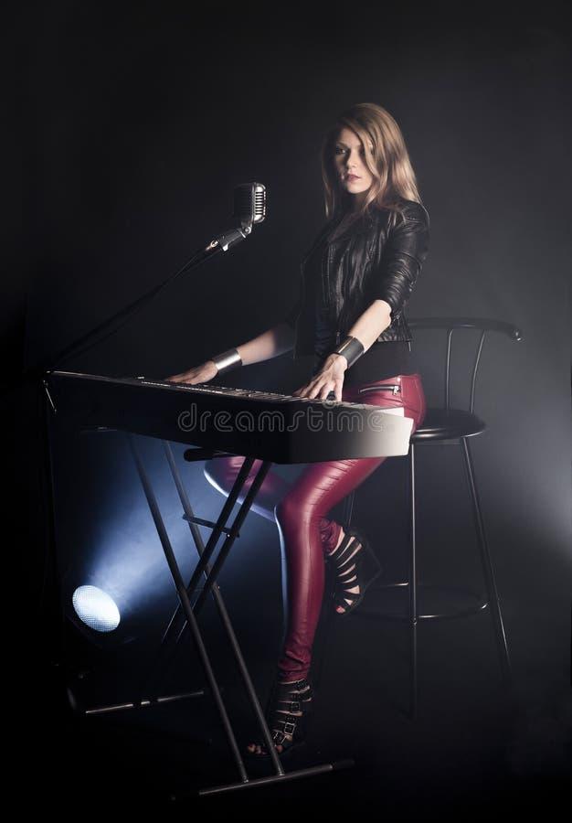 白肤金发的女孩音乐家钢琴演奏家戏剧在白色数字式钢琴执行,坐椅子,唱歌入减速火箭的话筒 妇女 免版税库存图片